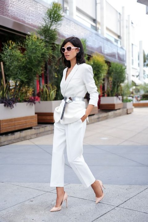 a modern white pantsuit with a deep neckline, a metallic belt and nude shoes