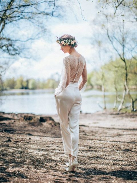 a romantic bridal jumpsuit with a lace bodice with long sleeves and buttons and shiny pants plus heels