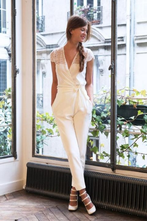 a romantic bridal jumpsuit with lace cap sleeves, a half lace bodice and a V-neckline, strappy heels