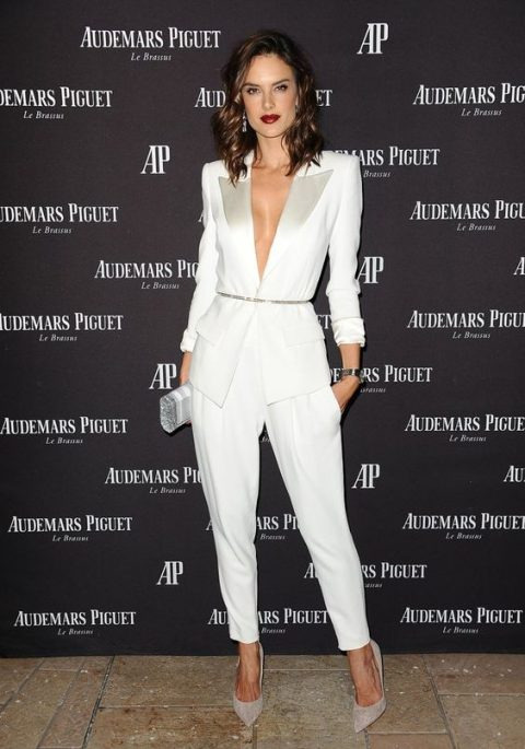 a sexy modern white jumpsuit with shiny lapels and pockets plus off-white shoes and a clutch