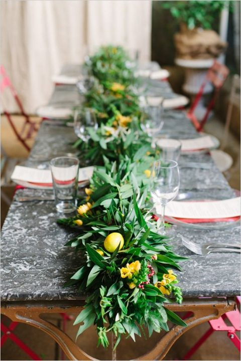 a textural greenery runner with yellow blooms and lemons