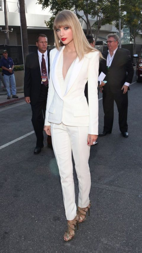 a white pantsuit with a plunging neckline and metallic shoes