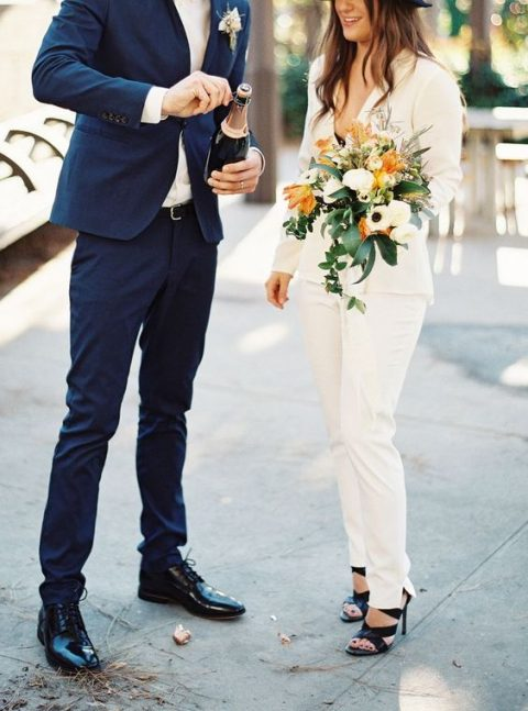 an ivory pantsuit with a deep V neckline and black heels