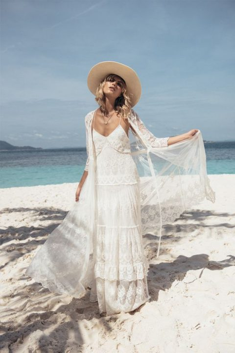 a boho lace spaghetti strap wedding gown with a matching coverup and a hat