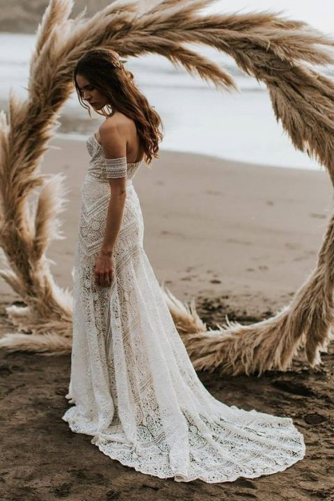 a boho lace strapless wedding dress with a train and arm straps for a boho feel