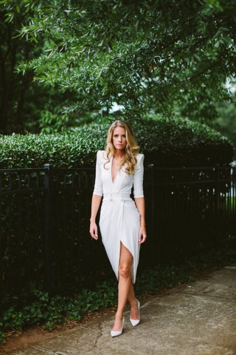 a gorgeous modern white dress with sculptural shoulders, a plunging neckline, a slit plus white heels