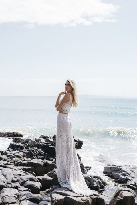 a lace two piece wedding dress with a crop top and a maxi skirt