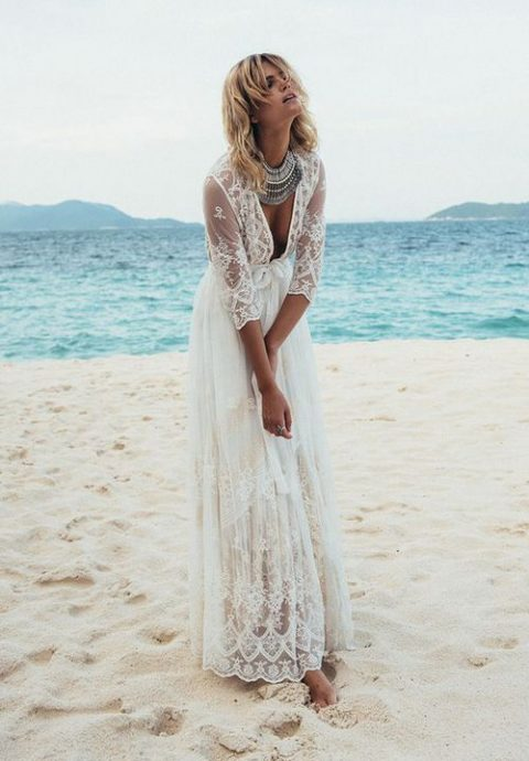a lace wedding dress with long sleeves, a plunging neckline a statement necklace