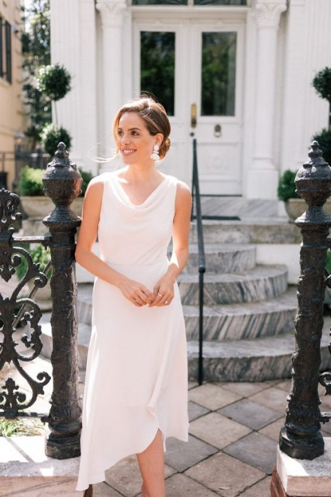 a light and airy white sleeveless dress with an asymmetrical skirt and statement earrings