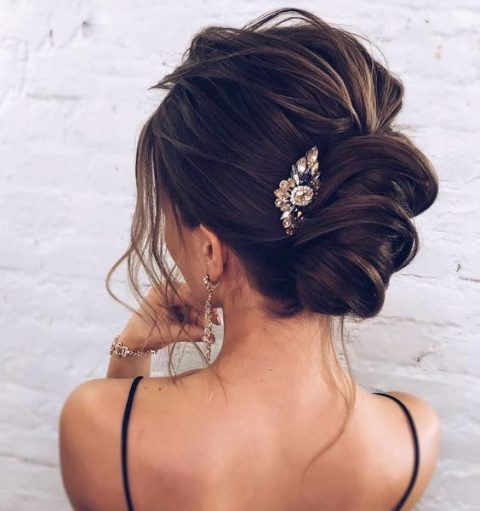 a low messy twisted updo with locks down and a large rhinestone hairpiece