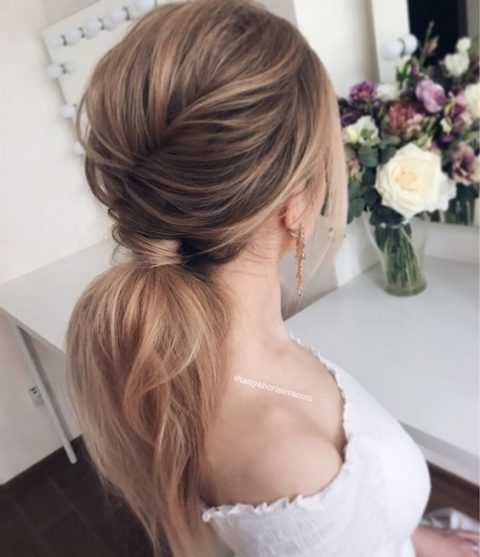 a low ponytail with a bump,volume and texture for a casual romantic look