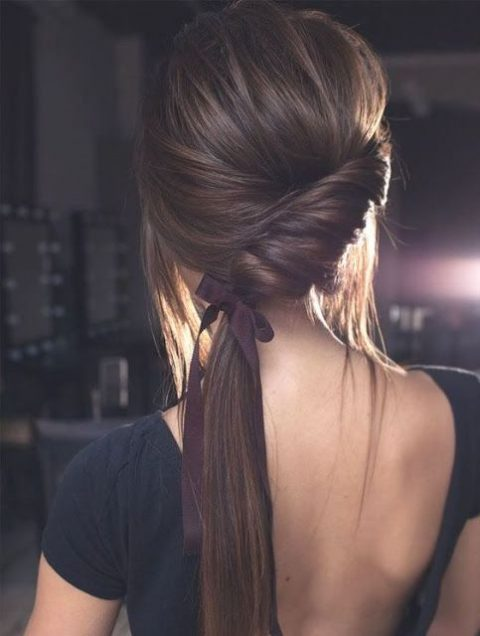 a low twisted ponytail with a bump and some hair down