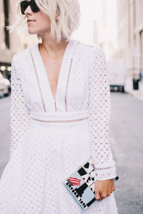 a mini dress with long sleeves, a plunging neckline and perforations for a boho bride