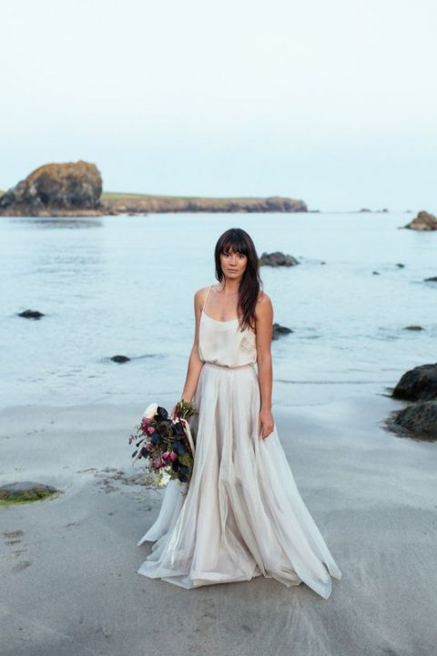 a modern and relaxed wedding dress with spaghetti straps and a layered skirt