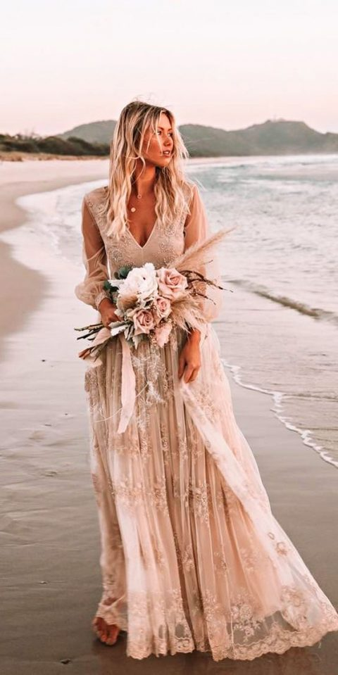 a nude wedding dress with sheer sleeves, a V-neckline, a lace maxi skirt and an embellished bodice