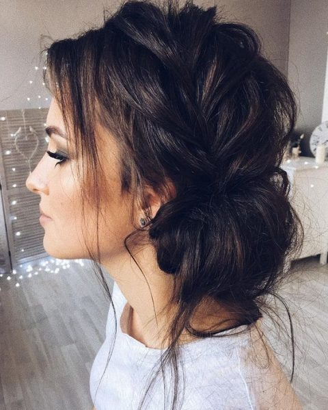 a side braided low updo with some bangs is a very chic idea