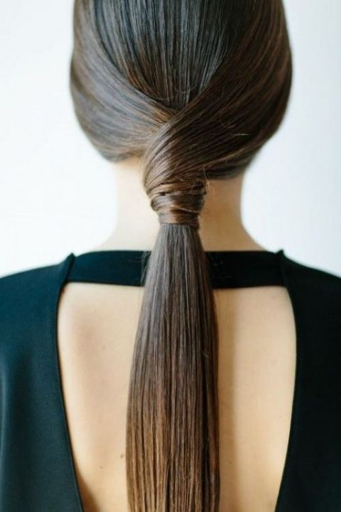 a sleek low twisted ponytail for a minimalist bride