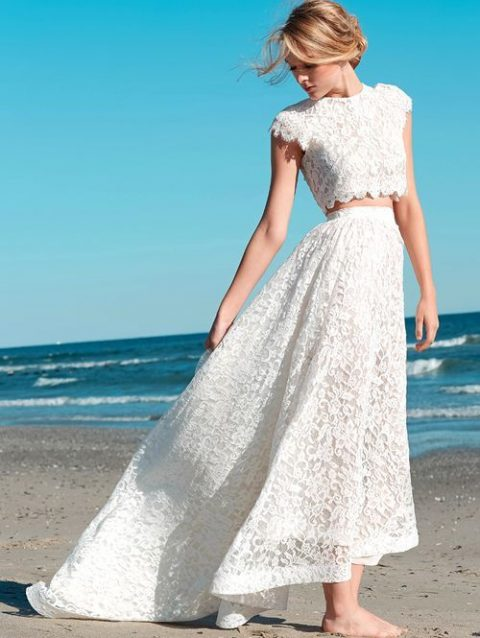a two piece lace wedding dress with a cap sleeve crop top and an A-line high low skirt