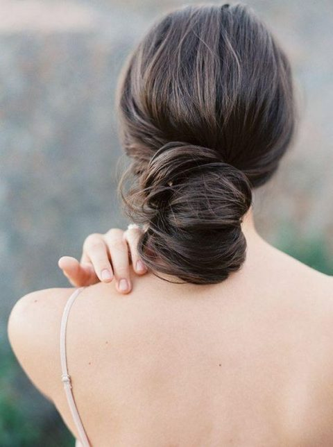 a very low and wavy chignon hairstyle with a bump on top
