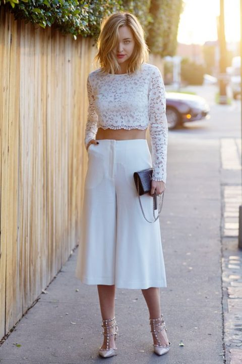 a white lace crop top with long sleeves, cropped culottes, blush studded shoes and a black clutch