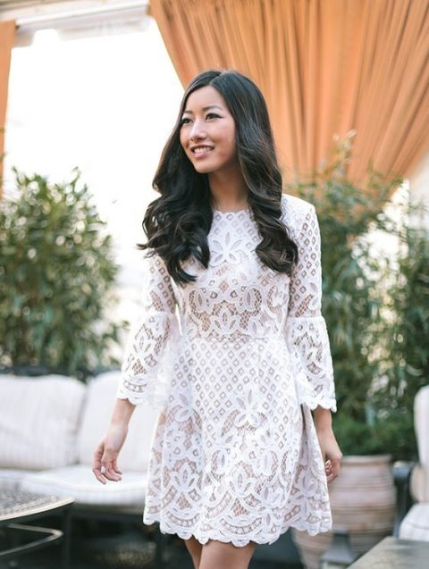 a white lace over the knee dress with bell sleeves and a high neckline to show off the legs