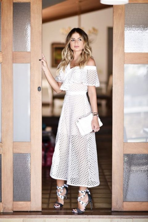 an off the shoulder white midi dress with sheer detailing, a white clutch and bold shoes