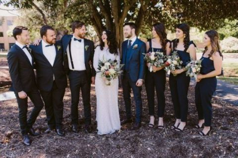 black jumpsuits with bow ties on the shoulders for bridesmaids and black tuxedos for groomsmen