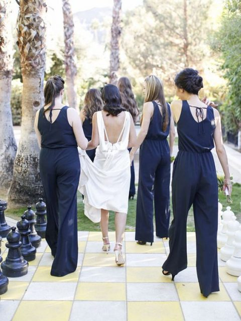 bridesmaids wearing navy jumpsuits with ties on the back for an elegant modern feel