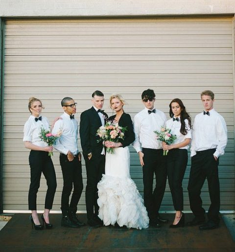 groomsmen and bridesmaids dressed in black plants, white shirts and bow ties for a chic look