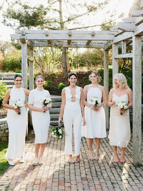 mismatched bridesmaids_ outfits and a white jumpsuit with a lace up neckline for the maid of honor