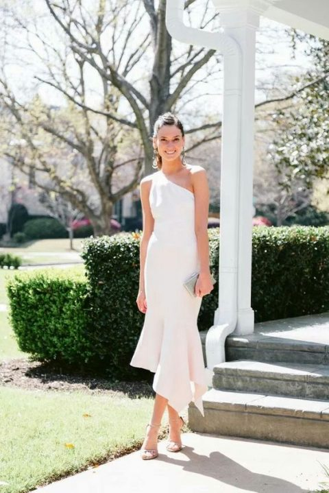 one shoulder sheath white dress with a ruffled asymmetrical skirt, statement earrings and a shoes