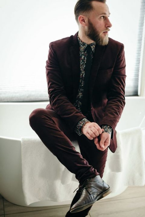 a burgundy suit, a black tie, a dark floral shirt and brown boots for a moody wedding