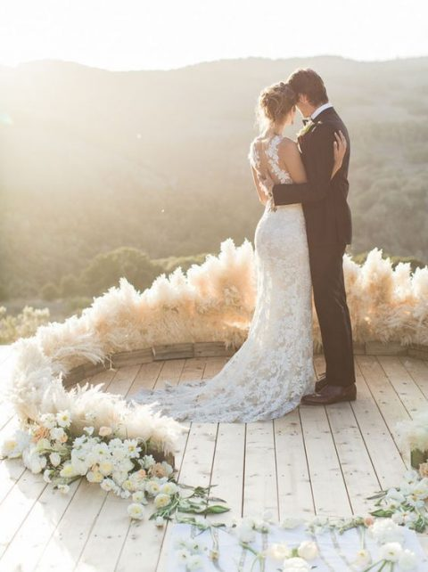 a chic semi circular wedding arch of pampas grass and neutral blooms