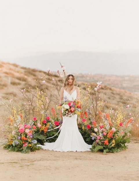 a colorful bright wedding altar of bold blooms, grasses and greenery for a desert wedding