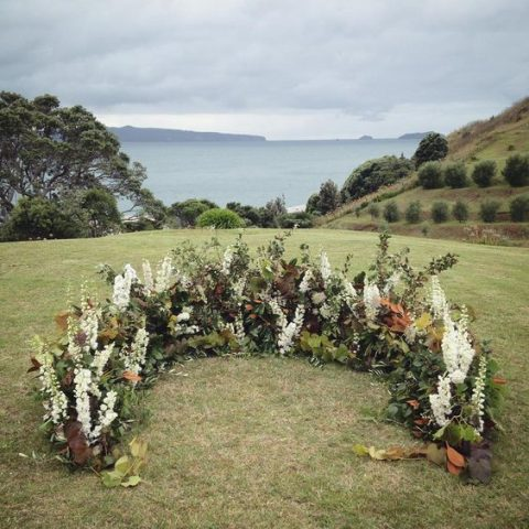 a fall-like semi circular wedding arch of white blooms and leaves of all shades