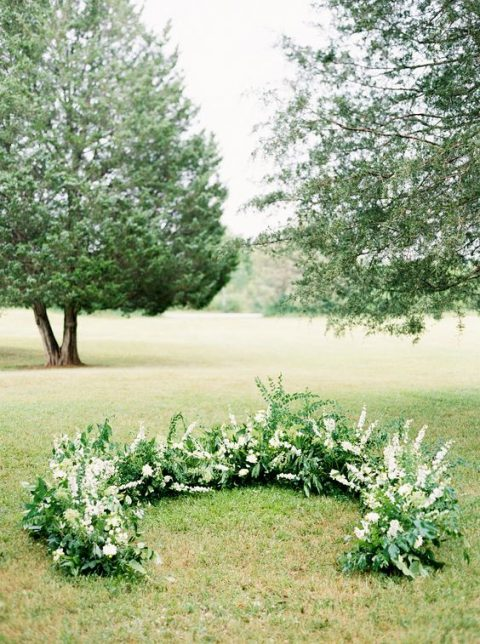 a fresh semi circular wedding altar of greenery and white blooms