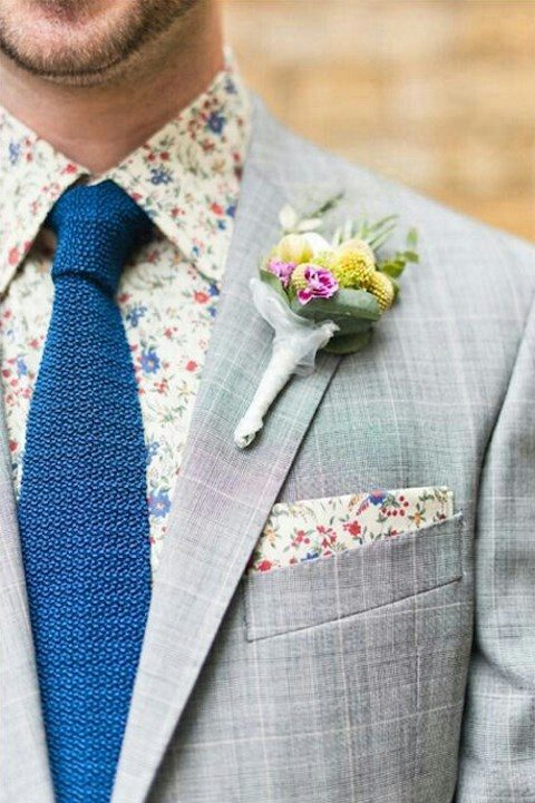 a grey checked suit, a retro-inspired floral print shirt, a blue tie