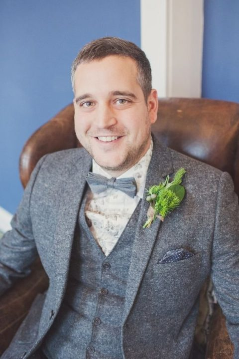 a grey wool three-piece suit, a grey bow tie and a light floral printed shirt