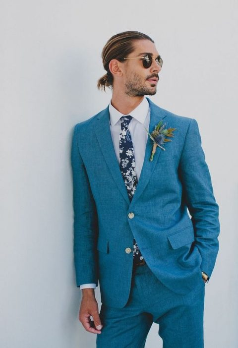 a light blue suit, a floral tie and a white shirt plus a trendy hairstyle