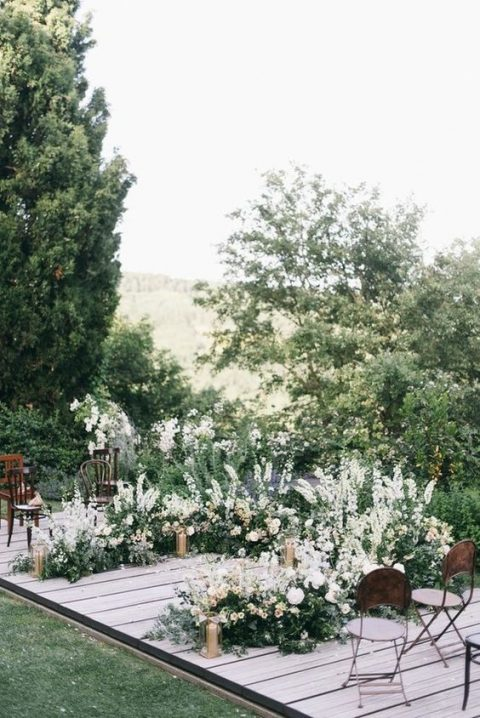 a lush semi circle wedding arch of white and blush blooms, greenere and candles