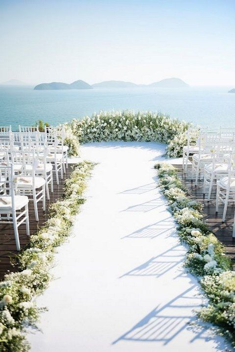 a luxurious greenery and white flower semi circular weddingarch for a seaside wedding