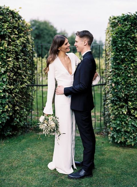 a modern plain wedding dress with bell sleeves and a plunging neckline