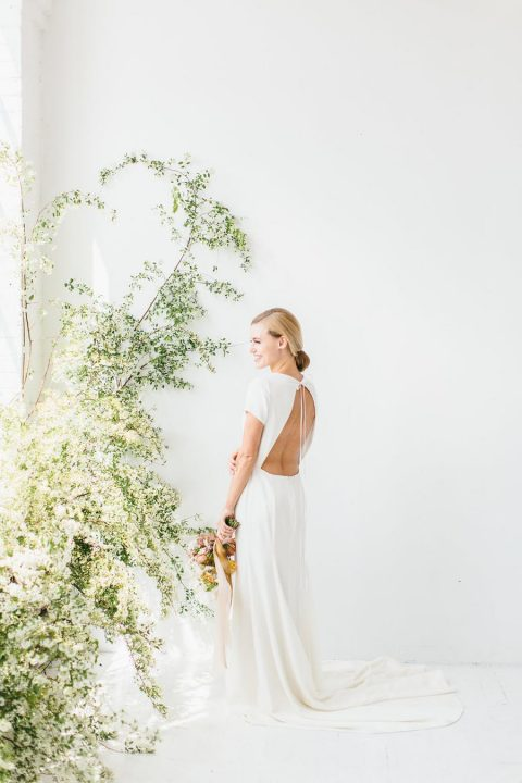 a modern plain wedding dress with short sleeves and a cutout back on ties