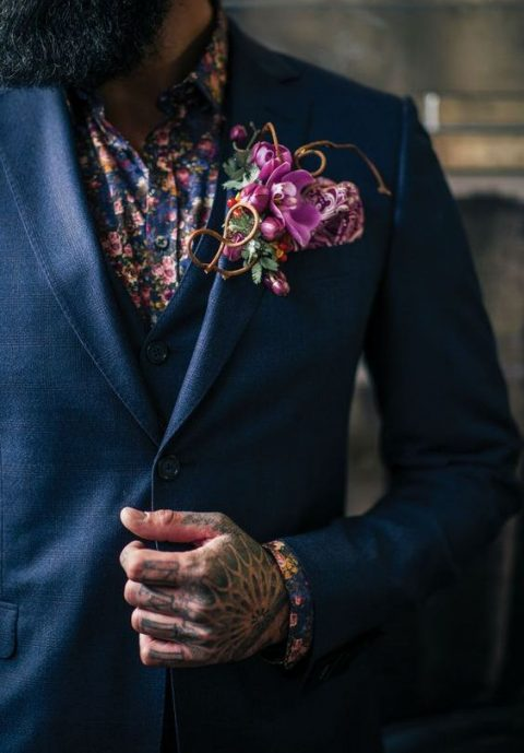 a navy three-piece suit, a dark floral shirt and a bold pink floral boutonniere