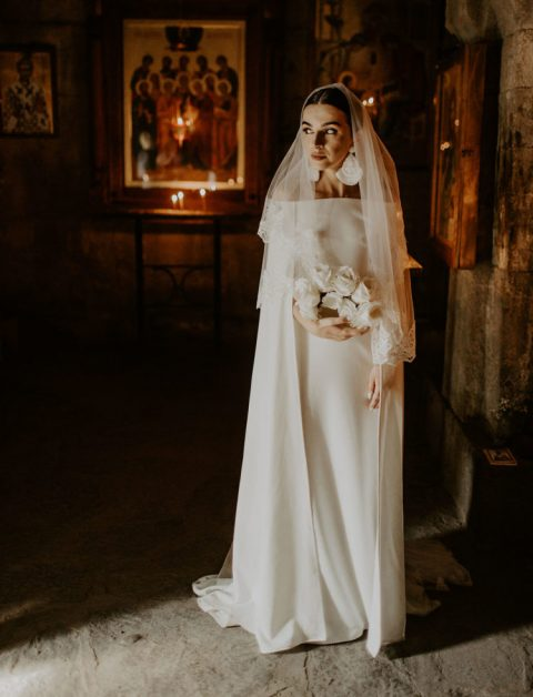 a plain off the shoulder wedding dress with long sleeves and a cape attached