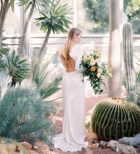 a plain wedding dress with long sleeves, a high neckline and a cutout back plus a train