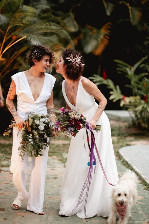 a plain wedding dress with thick straps and a plunging neckline and a plain wedding jumpsuit