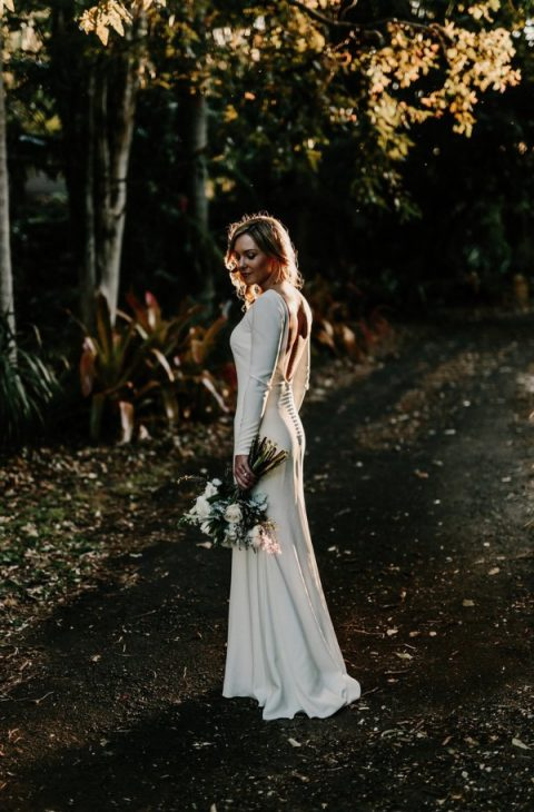 a plain wedding gown with long sleeves and an open back on buttons