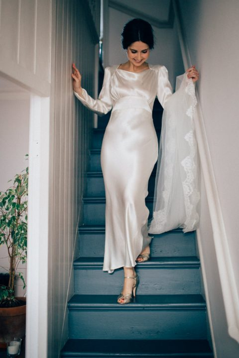 a refined bridal look with a plain silk wedding dress, long sleeves and silver shoes