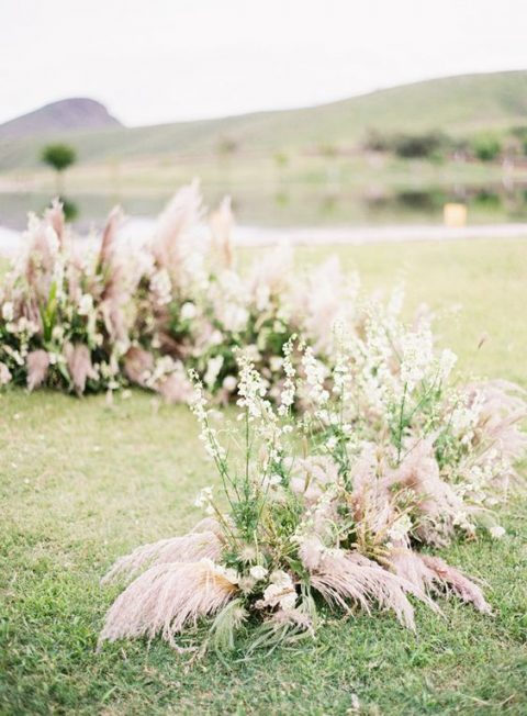 a relaxed summer semi circular wedding altar of wildflowers and pink grasses and herbs